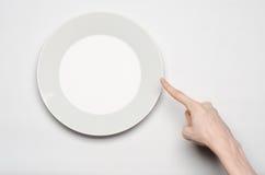 Θέμα εστιατορίων και τροφίμων: το ανθρώπινο χέρι παρουσιάζει χειρονομία σε ένα κενό άσπρο πιάτο σε ένα άσπρο υπόβαθρο απομονωμένη Στοκ Εικόνες