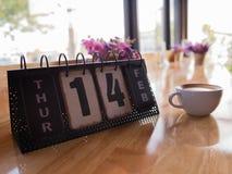 Θέμα ημέρας βαλεντίνου με το ξύλινο ημερολόγιο φραγμών και τον καυτό καφέ στον καφέ στοκ εικόνες