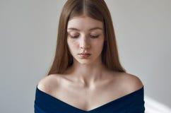 Θέμα ομορφιάς: πορτρέτο ενός όμορφου νέου κοριτσιού με τις φακίδες στο πρόσωπό της και τη φθορά ενός μπλε φορέματος σε ένα άσπρο  Στοκ Φωτογραφίες