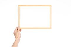 Θέμα πλαισίων διακοσμήσεων και φωτογραφιών σπιτιών: ανθρώπινο χέρι που κρατά ένα ξύλινο πλαίσιο εικόνων απομονωμένο σε ένα άσπρο  Στοκ Εικόνες