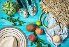 Θέμα υποβάθρου θερινών διακοπών με την τσάντα, το καπέλο, την καρύδα, τα γυαλιά ηλίου και τα ροδάκινα στο μπλε ξύλινο υπόβαθρο στοκ εικόνες