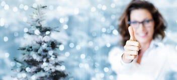 Θέμα Χριστουγέννων, επιχειρησιακή χαμογελώντας γυναίκα όπως το χέρι με τον αντίχειρα επάνω Στοκ Εικόνες
