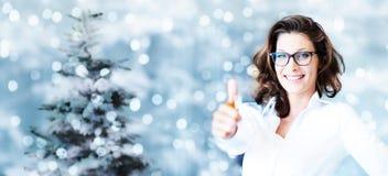 Θέμα Χριστουγέννων, επιχειρησιακή χαμογελώντας γυναίκα όπως το χέρι με τον αντίχειρα επάνω Στοκ Φωτογραφίες