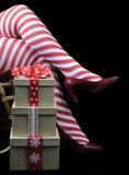 Θέμα Χριστουγέννων κυρία Santa με τα κόκκινα και άσπρα πόδια και τα δώρα γυναικείων καλτσών λωρίδων καλάμων καραμελών Στοκ Εικόνες