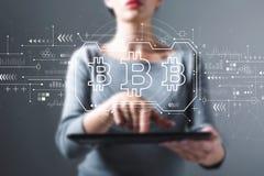 Θέμα Bitcoin με τη γυναίκα που χρησιμοποιεί μια ταμπλέτα στοκ φωτογραφίες