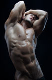 Θέμα Bodybuilder και λουρίδων: όμορφος με την αντλημένη τοποθέτηση ατόμων μυών γυμνή στο στούντιο σε ένα σκοτεινό υπόβαθρο Στοκ Φωτογραφία