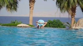 Θέρετρο πολυτέλειας Χαλάρωση γυναικών στο νερό πισινών απείρου Όμορφο ευτυχές υγιές θηλυκό πρότυπο καλοκαίρι απόλαυσης απόθεμα βίντεο