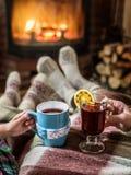 Θέρμανση και χαλάρωση κοντά στην εστία με ένα φλυτζάνι του ζεστού ποτού στοκ εικόνα