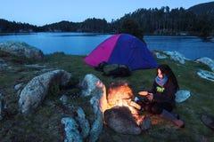 Θέρμανση κοριτσιών δίπλα σε μια φωτιά Στοκ Εικόνα