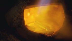 Θέρμανση του πολύτιμου μετάλλου σε μια υγρή κατάσταση στη χοάνη στο μεταλλουργικό κατάστημα Ο επιδέξιος εργαζόμενος προσθέτει τα  απόθεμα βίντεο