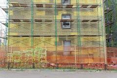 Θέρμανση των εξωτερικών τοίχων του κτηρίου με μια μόνωση ρόλων Για διευκόλυνση των εργαζομένων, τα ικριώματα εγκαθίστανται στο τ στοκ φωτογραφίες με δικαίωμα ελεύθερης χρήσης
