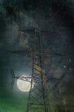 Θέση ηλεκτρικής ενέργειας σκιαγραφιών με το φεγγάρι και γαλακτώδης τρόπος στη νύχτα Στοκ Φωτογραφίες