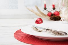 Θέση Χριστουγέννων που θέτει με το άσπρο dishware, τα μαχαιροπήρουνα, τις ασημικές και τις κόκκινες διακοσμήσεις στον ξύλινο πίνα στοκ εικόνα με δικαίωμα ελεύθερης χρήσης