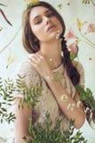 Θέτοντας γυναίκα πίσω από το παράθυρο με τα ξηρά λουλούδια Στοκ Εικόνα