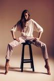 Θέτοντας γυναίκα στα ριγωτά εσώρουχα στην καρέκλα στο στούντιο Στοκ φωτογραφία με δικαίωμα ελεύθερης χρήσης