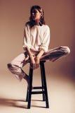 Θέτοντας γυναίκα στα ριγωτά εσώρουχα στην ξύλινη καρέκλα Στοκ φωτογραφία με δικαίωμα ελεύθερης χρήσης