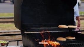 Θέτοντας πυρκαγιά στη σχάρα για το τηγάνισμα του ακατέργαστων κρέατος και των κουλουριών για Burgers φιλμ μικρού μήκους