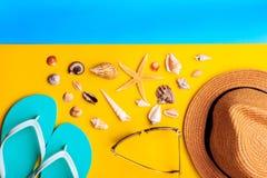 Θαλασσινά κοχύλια και αστέρια Παντόφλες καπέλων αχύρου και μεντών στο κίτρινο και μπλε υπόβαθρο στοκ φωτογραφία
