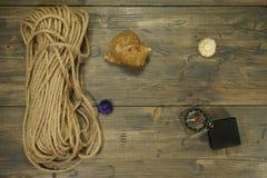Θαλασσινό κοχύλι σχοινιών, πυξίδων και σαλιγκαριών σε έναν ξύλινο πίνακα στοκ φωτογραφία με δικαίωμα ελεύθερης χρήσης