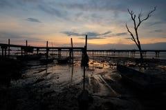 Θαυμάσια άποψη της ανατολής στο υγρό έδαφος με το υπόβαθρο λιμενοβραχιόνων στοκ εικόνες