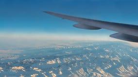 Θαυμάσια άποψη των βουνών χιονιού Tian Shan μέσω του παραθύρου ένα αεροπλάνο στοκ φωτογραφία με δικαίωμα ελεύθερης χρήσης