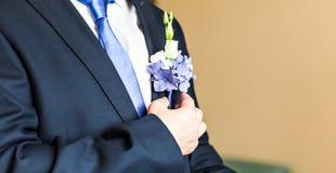 Θαυμάσια γαμήλια μπουτονιέρα σε ένα κοστούμι της κινηματογράφησης σε πρώτο πλάνο νεόνυμφων στοκ εικόνες
