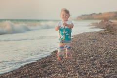 Θαυμάσια εικόνα ονείρου του κοριτσάκι με τα μπλε μάτια ξανθών μαλλιών και τα ρόδινα μάγουλα που θέτουν το τρέξιμο από την παραλία Στοκ Εικόνες