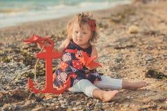 Θαυμάσια εικόνα ονείρου του κοριτσάκι με τα μπλε μάτια ξανθών μαλλιών και τα ρόδινα μάγουλα που θέτουν το τρέξιμο από την παραλία Στοκ εικόνες με δικαίωμα ελεύθερης χρήσης
