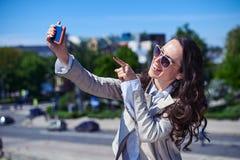 Θαυμάσια κυρία που παίρνει selfie μπροστά από το πανόραμα πόλεων Στοκ Εικόνες