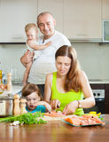 Θαυμάσια τετραμελής οικογένεια που μαγειρεύει τα κόκκινα ψάρια στην εγχώρια κουζίνα Στοκ Εικόνα