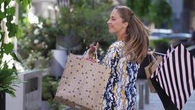 Θαυμάσιες περιστροφές brunette γύρω με τις τσάντες αγορών της Αρκετά νέα γυναίκα που περπατά στην πόλη σε αργή κίνηση 4k φιλμ μικρού μήκους