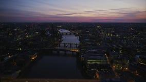 Θαυμάσιος ρόδινος ουρανός ηλιοβασιλέματος πέρα από τον ποταμό Τάμεσης στο φωτεινό νύχτας ελαφρύ εναέριο πανόραμα αρχιτεκτονικής τ φιλμ μικρού μήκους