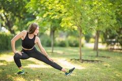 Θαυμάσιο, ευτυχές και όμορφο φίλαθλο κορίτσι που κάνει το τέντωμα στο πράσινο πάρκο το πρωί Η λεπτή γυναίκα φαίνεται αναζωογονώντ Στοκ Εικόνες