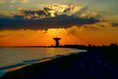 Θαυμάσιο ηλιοβασίλεμα στο υπόβαθρο της θάλασσας και της διαστημικής κεραίας στοκ εικόνα