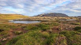 Θαυμάσιο ισλανδικό τοπίο έδαφος χλόης, λίμνη, υψηλά πολύχρωμα βουνά, και όμορφος ουρανός Στοκ Φωτογραφίες
