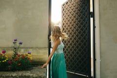 Θαυμάσιο ξανθό κορίτσι με την κυματιστή τρίχα στην κίνηση, που θέτει στον ήλιο Στοκ Φωτογραφία