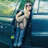 Θαυμάσιο ξανθό κορίτσι οδηγών με τα γυαλιά ηλίου που κάθεται στο BL Στοκ Φωτογραφία