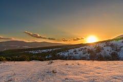 Θαυμάσιο πορτοκαλί ηλιοβασίλεμα στα χιονισμένα βουνά Ρωσία, Stary Krym Στοκ εικόνες με δικαίωμα ελεύθερης χρήσης