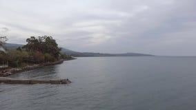 Θαυμάσιο τοπίο της θάλασσας, γραμμή ακτών, πράσινος λόφος στο ηλιοβασίλεμα με το νεφελώδη ουρανό απόθεμα βίντεο