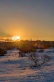 Θαυμάσιο χειμερινό πορτοκαλί ηλιοβασίλεμα στο χιονισμένο τομέα με τον ήλιο από τα σύννεφα που κλείνει Ρωσία, Stary Krym Στοκ εικόνα με δικαίωμα ελεύθερης χρήσης