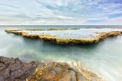Θαυμάσιο seascape με τα κύματα θάλασσας που χτυπούν το μεγάλο βράχο Στοκ Φωτογραφίες