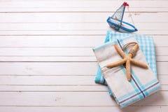 Θαλάσσια στοιχεία στην μπλε πετσέτα και διακοσμητικό σκάφος στο άσπρο ξύλινο β Στοκ φωτογραφία με δικαίωμα ελεύθερης χρήσης