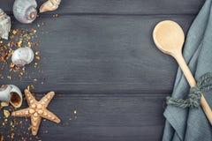Θαλασσινά κοχύλια, ξύλινες κουτάλι και πετσέτα πιάτων στο μπλε ξύλινο Στοκ Φωτογραφία