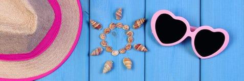 Θαλασσινά κοχύλια στη μορφή του ήλιου, γυαλιά ηλίου και καπέλο αχύρου στους μπλε πίνακες, εξαρτήματα για το καλοκαίρι Στοκ Εικόνα