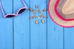 Θαλασσινά κοχύλια στη μορφή του ήλιου, γυαλιά ηλίου και καπέλο αχύρου στους μπλε πίνακες, εξαρτήματα για το καλοκαίρι, διάστημα α Στοκ Εικόνες