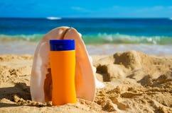 Θαλασσινό κοχύλι και sunscreen στην αμμώδη παραλία Στοκ Φωτογραφία