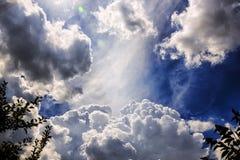Θεία σύννεφα σε μια άποψη μπλε ουρανού από έναν κήπο στοκ εικόνες