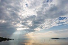 Θεαματική άποψη μιας λίμνης, με τα σύννεφα, τις ακτίνες ουρανού και ήλιων που απεικονίζουν στο νερό Στοκ φωτογραφία με δικαίωμα ελεύθερης χρήσης