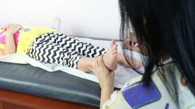 Θεράπων που δίνει το μασάζ στο πόδι κοριτσιών Μασάζ σε ένα μικρό κορίτσι απόθεμα βίντεο