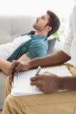 Θεράπων που παίρνει τις σημειώσεις για τον ανησυχημένο ασθενή του στοκ εικόνα με δικαίωμα ελεύθερης χρήσης